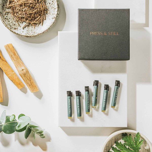 Press & Still's aromatherapy exploration set featuring essential oil blends Balance, Comfort, Inspire, Refresh, Relax, Sleep. Surrounded by fresh geranium and eucalyptus leaves, palo santo wood and vetiver.
