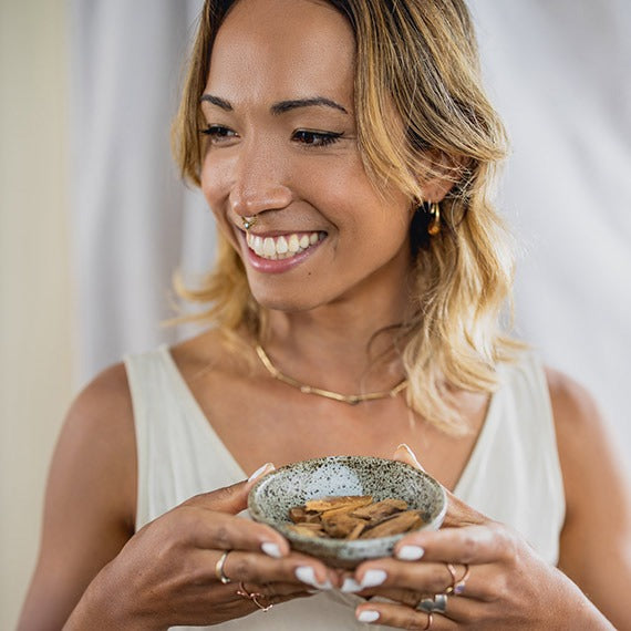 Woman holding a ceramic bowl with fragrant, calming sandalwood chips..