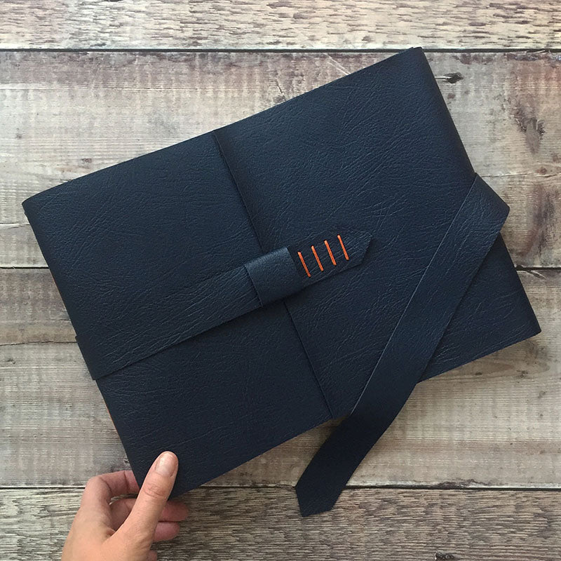 Leather Memory Book in Navy Blue and Orange against wood background