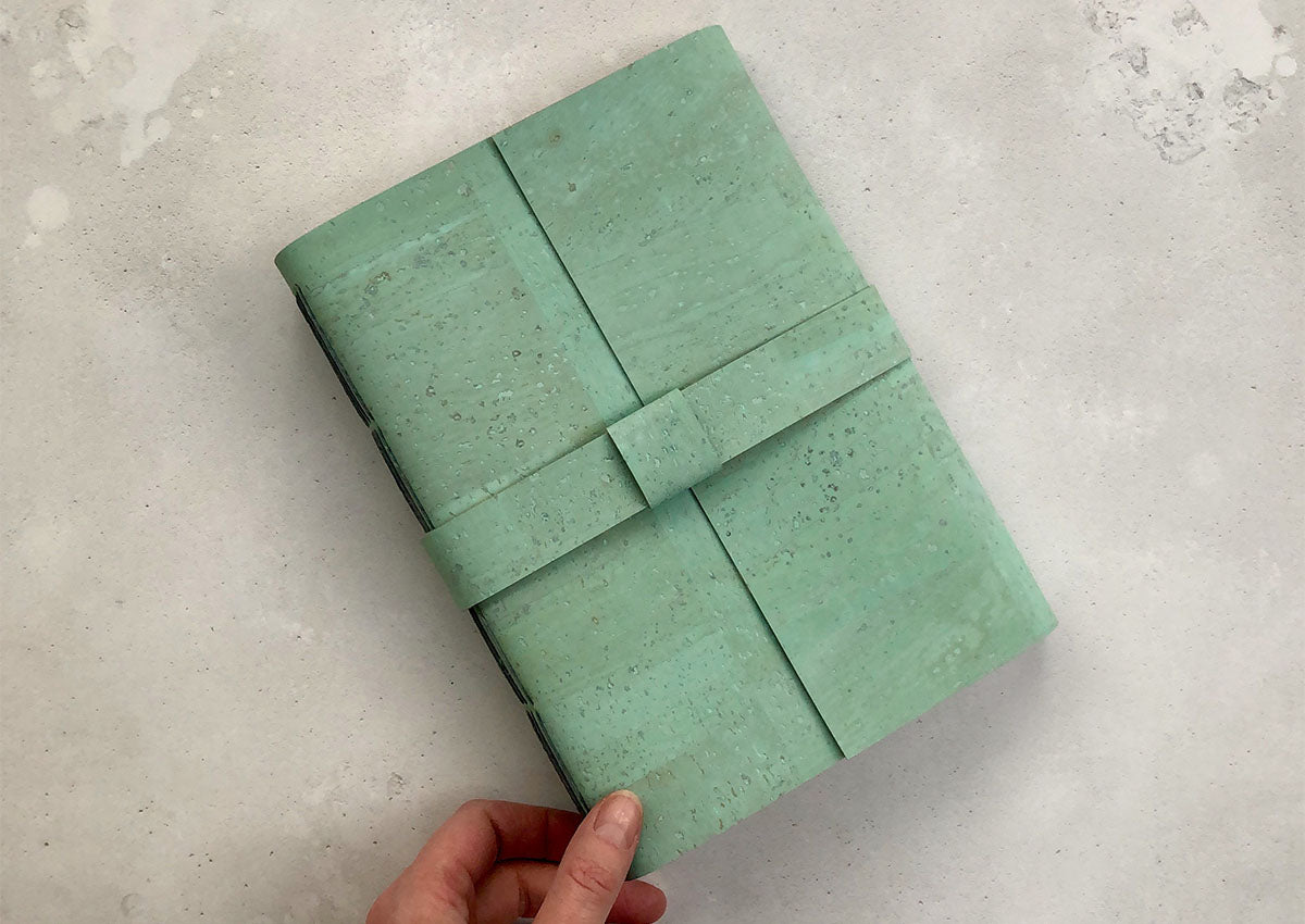 Cork Vegan Journal: Mint Green and Grey showing Longstitch spine held in the hand.