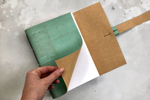 Hand turns the page of a softcover vegan journal handmade in cork textile