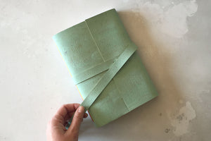 Hand undoes strap on a5 portrait mint green sketchbook