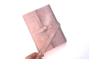 Hand holds strap of Cork Sketchbook in Rose Gold cork textile