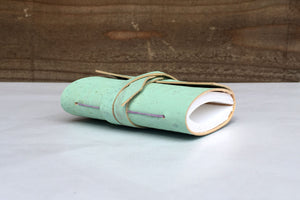 Lilac spine stitching on small handmade cork journal in mint green, shown at an angle
