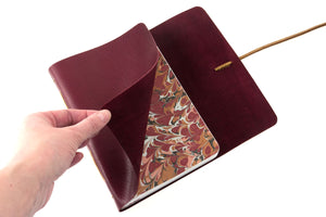 Handmade leather bound notebook with marbled endpapers in brown, tan and maroon.