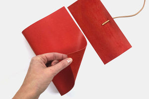 Hand turns cover to reveal pages of leather journal