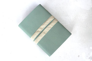 Natural unbleached woven linen ribbon keeps leather sketchbook closed.