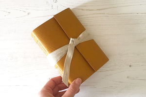 Hand holds A6 Journal or Sketchbook bound in Mustard Yellow leather with linen ribbon