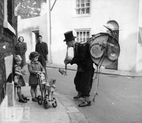 Vintage photo of a one man band performing for little kids