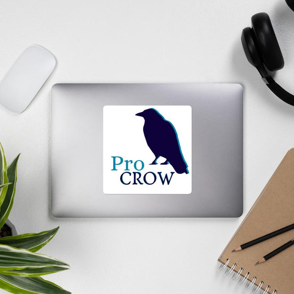"""A Jumbo white sticker is featured on a silver laptop on a grey background. The sticker features a shadowed silhouette of a crow and the words """" Pro Crow."""" This is a design by Amanda Ramsay. Around the laptop are a singular wireless mouse in white to the top left, a set of black padded headphones on the top right, a writing pads with instruments on the bottom right, and at the bottom left a plant's leaves poke into view."""