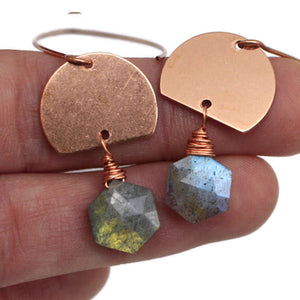 Grey Blue Labradorite beads in hexagon shape hang below half moon shaped copper sheet on middle and index finger