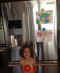 Lulalu Click Clips displaying kid's art on stainless steel refrigerator