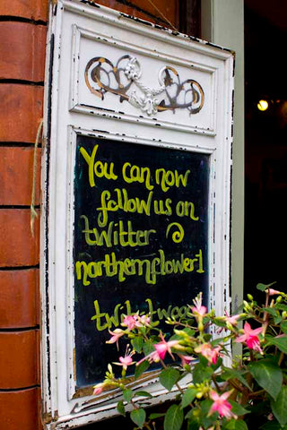 Close up of shop blackboard inviting customers to follow on Twitter @northernflower1