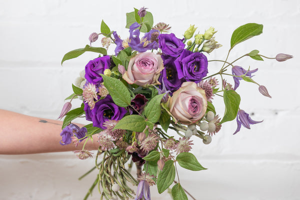 This sumptuous bouquet of purples and lilacs combines roses with clematis, anemones, astrantia, purple lisianthus and seasonal foliages.