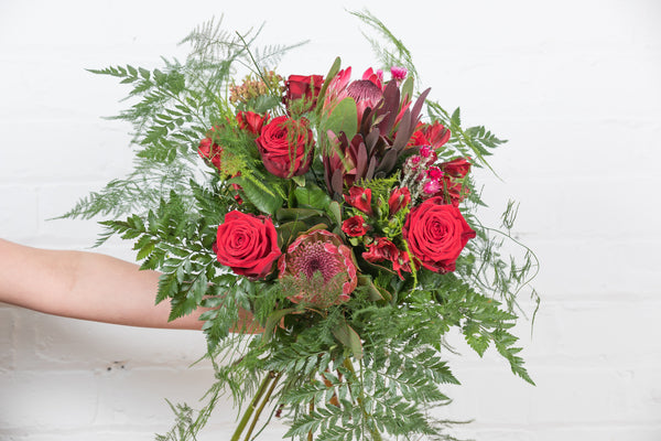 Red roses, protea, modern Valentine's bouquet, asparagus fern, trendy foliages