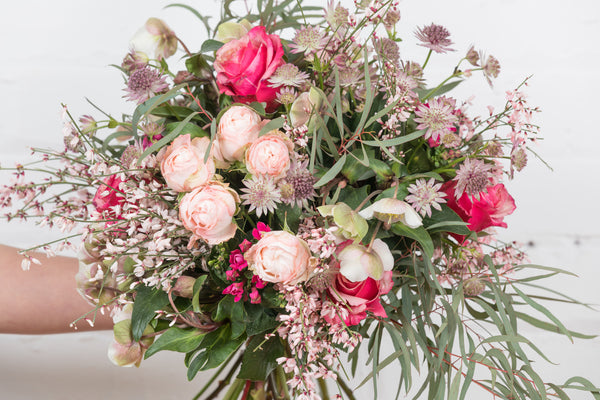 A mix of stunning roses and flowers including spray 'bombastic' roses, seasonal hellebores, astrantia, bouvardia and eucalyptus 'Nikolai'