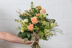 A delicate and pretty hand tied bouquet in soft peach tones of roses, hypericum, stocks, lisianthus and seasonal foliages, gift wrapped in complementary colours and tied with ribbon.