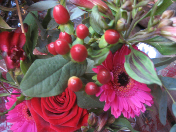 Close up hypericum berries, hot pink gerbera and red rose