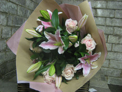 Bouquet of light pink lilies and roses wrapped in pink tissue and brown paper