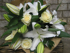 Bouquet of white lilies and roses wrapped in brown paper