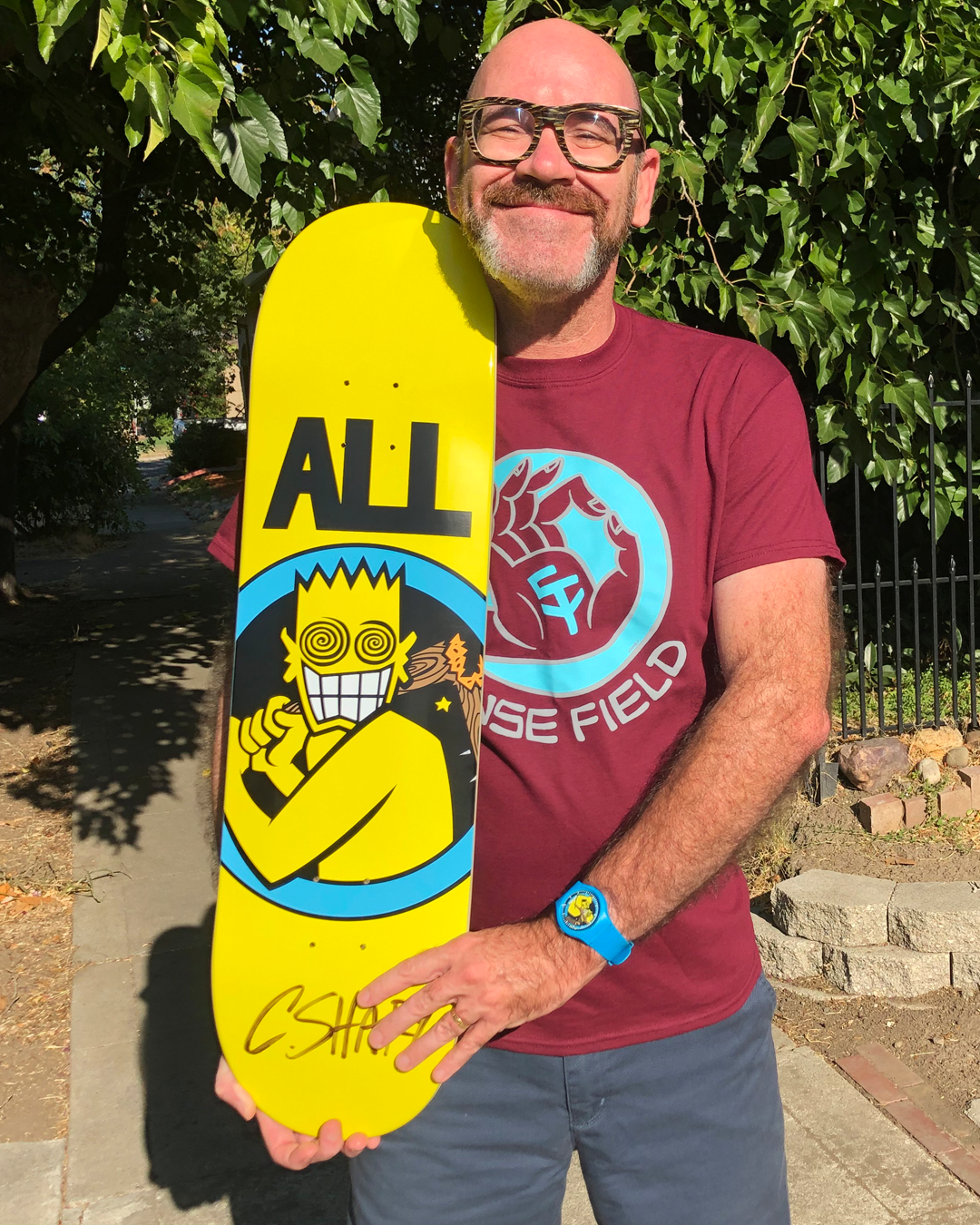Chris Shary holding autographed ALL skateboard deck