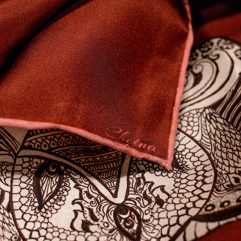 Close-up of Chetna Singh orange and rust tone elephant print long silk scarf.