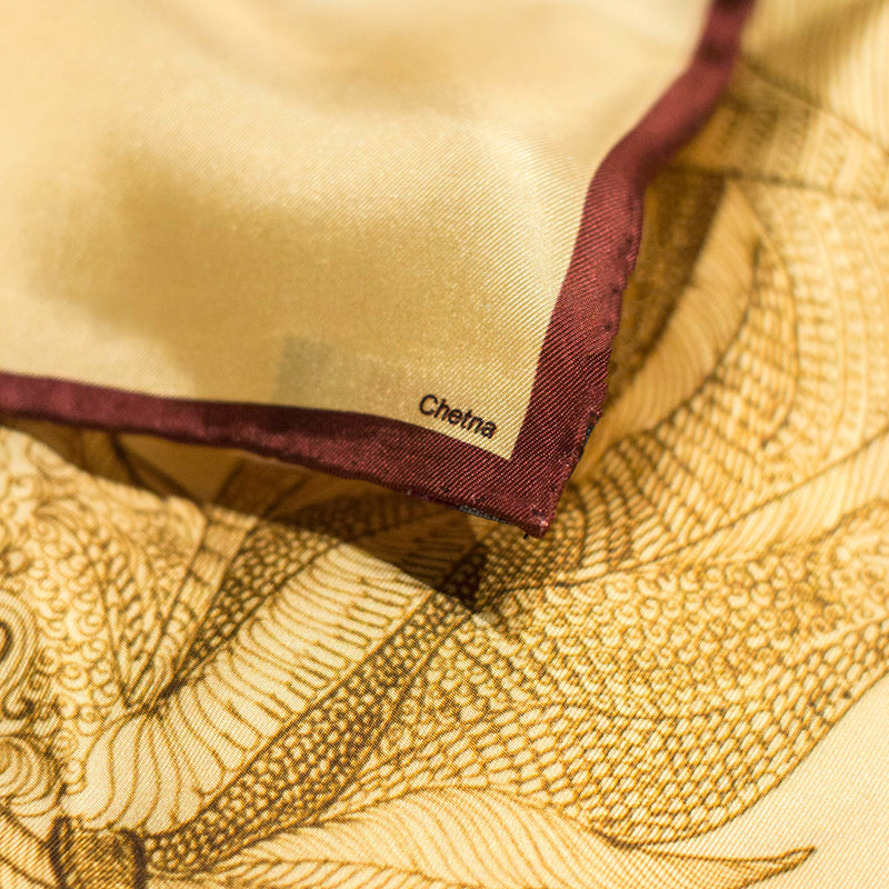 Close-up of Chetna Singh gold tone horse print square silk scarf.