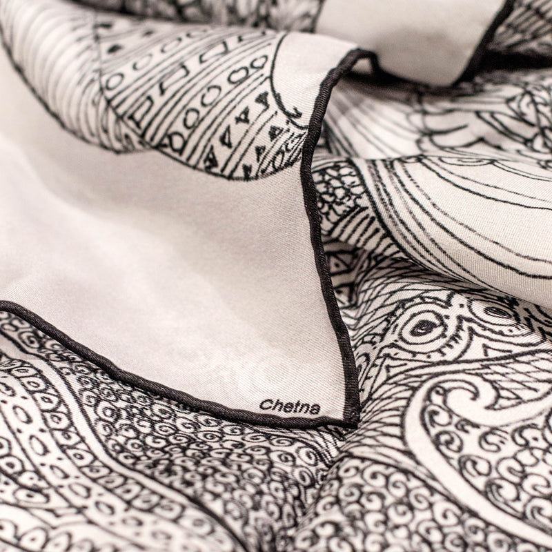 Close-up of Chetna Singh white henna horse print square silk scarf.