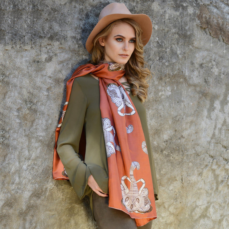 Model wearing Chetna Singh orange and rust tone elephant print long silk scarf.