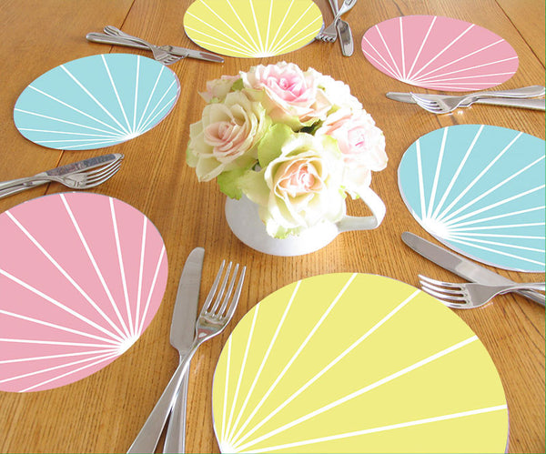 the table is set pastel pink blue yellow table mats place mat