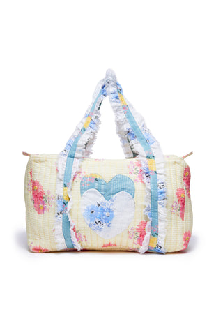 Yellow duffle bag with pink floral detail and long blue handles