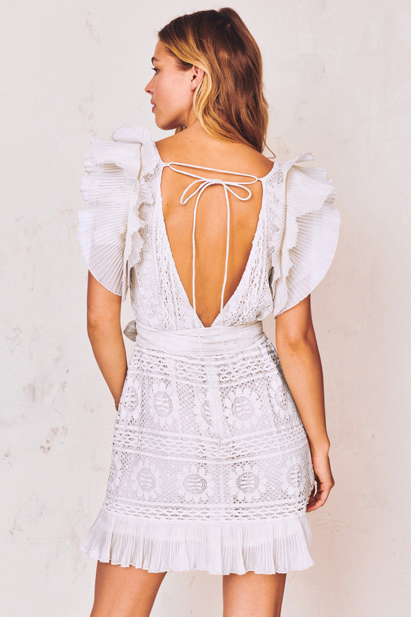 White lace detail mini dress with flutter ruffle trim sleeves, front tie bow, and deep V-neck with open tie back