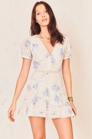Blue and white floral mini dress with tiered ruffled skirt and puffed short sleeves with deep V-neck and embroidery detail