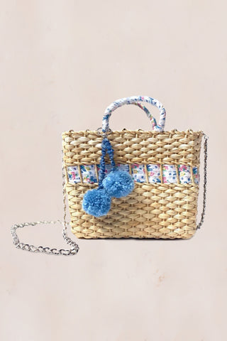 Handmade straw bag with blue and white floral print with decorative pompoms and crossbody chain