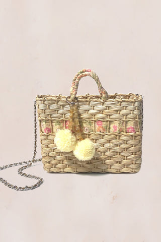 Handmade straw bag with yellow and pink floral print with decorative pompoms and crossbody chain