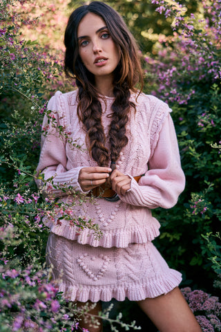 Pink cable knit sweater with ruffle detailing and heart cable design
