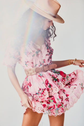 Pink floral print mini dress with button going down tiered ruffle skirt detail and flutter sleeves