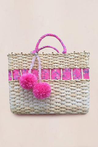 Handmade straw bag with pink floral print with decorative pompoms and crossbody chain
