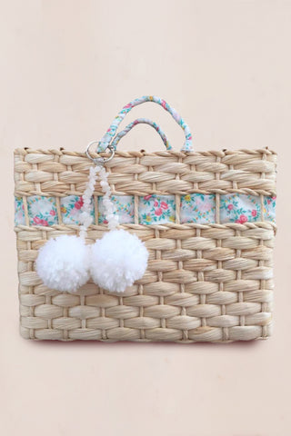 Handmade straw bag with green and white floral print with decorative pompoms and crossbody chain