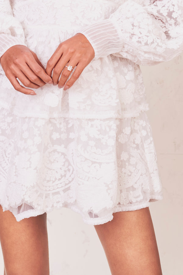 Fitted white lace mini dress with puffed long sleeves and tiered ruffle skirt