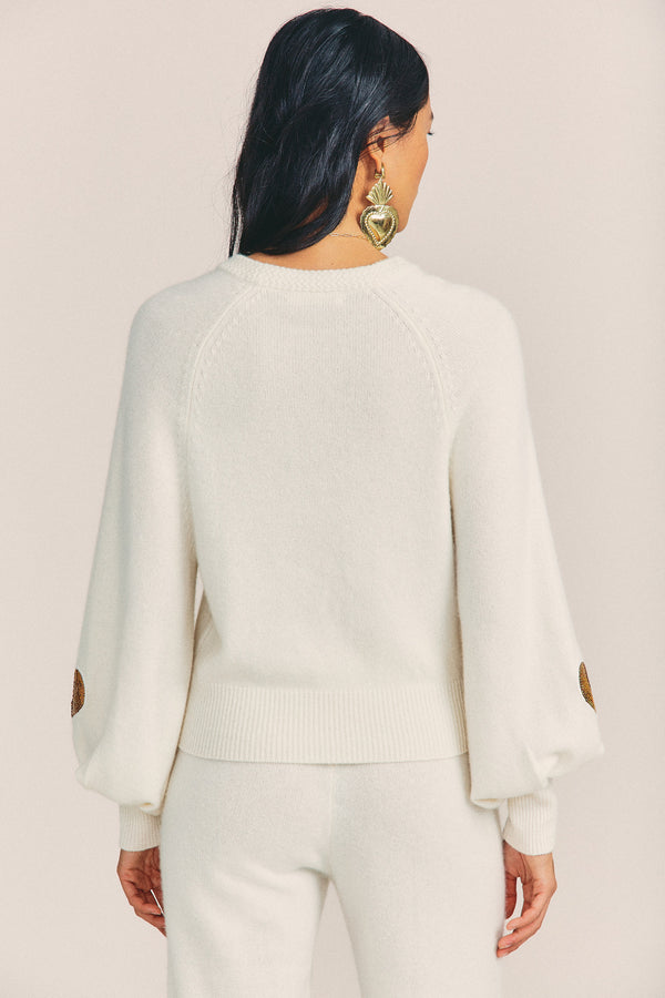 White cashmere-wool blend sweater with puffed long sleeves and gold sequin heart detail on sleeve