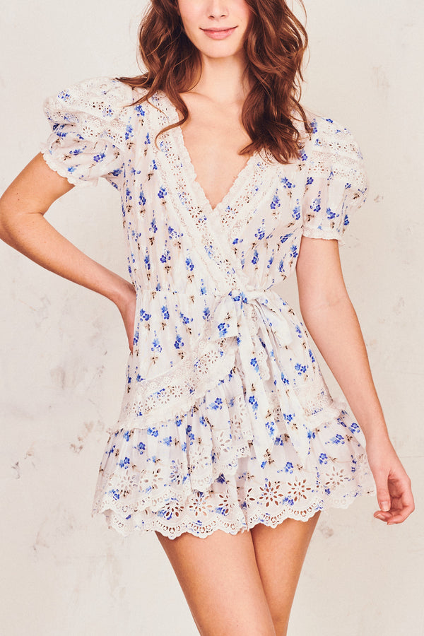 Blue and white floral mini front tie dress with puffed short sleeves and white embroidery detail and tiered ruffled bottom