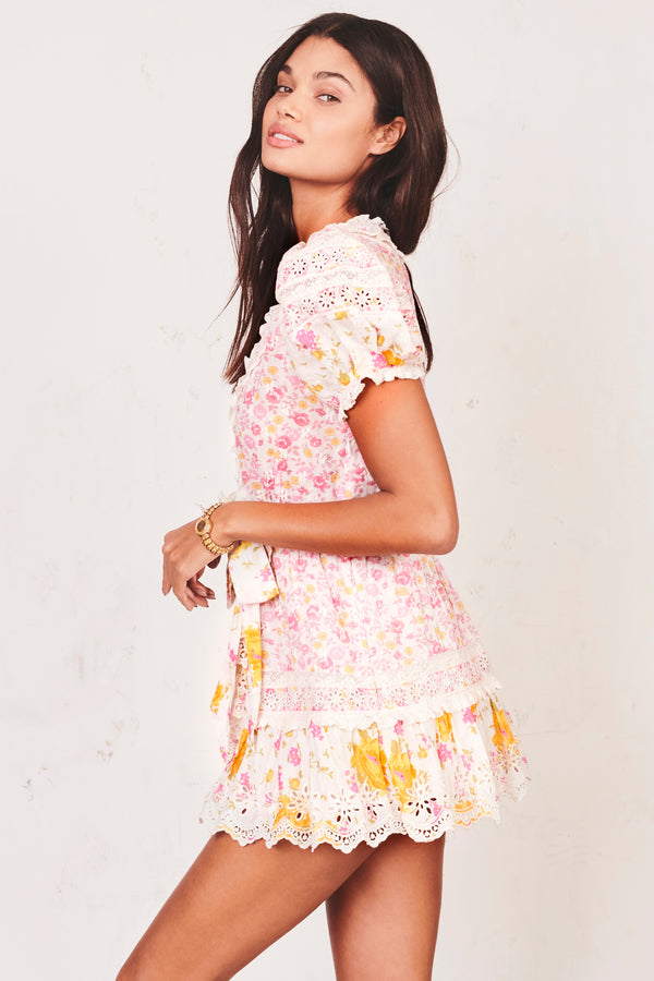 Pink, yellow and white floral mini tie front dress with puffed short sleeves and white embroidery detail and tiered ruffled bottom