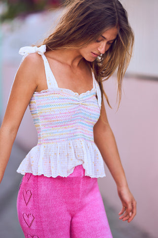 White and multi-colored shirred sweetheart neckline peplum tank with bows at the shoulder