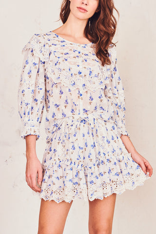 Blue and white floral print top with high neckline white embroidery detail and long puffed sleeves