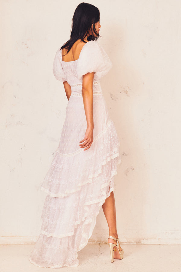 White lace high low dress with puffed short sleeve, fitted waist, and tiered ruffle skirt