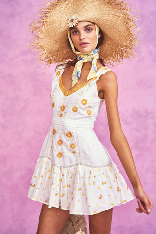 White mini dress with yellow embroidery detail and fitted waist