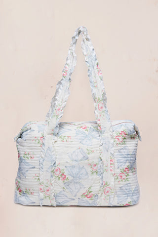 Blue duffle bag with pink floral print and ruffle trim handles