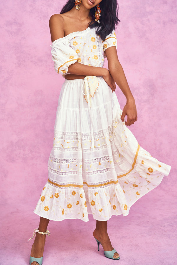 White tiered maxi skirt with yellow embroidery detail and elastic waist