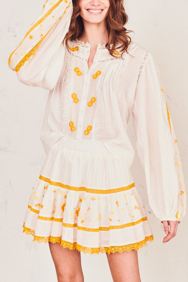 White tiered mini skirt with yellow embroidery detail and elastic waist
